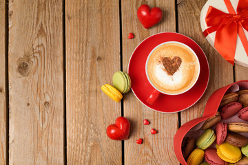 Valentines day concept with macarons and coffee cup over wooden background. Top view from above
