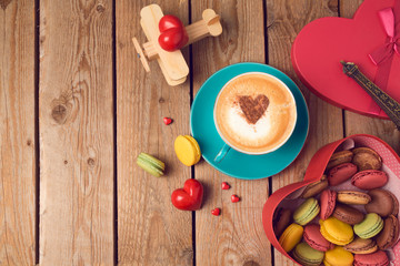 Valentines day concept with macarons, coffee cup and toy airplane over wooden background. Top view from above