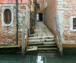 The ancient narrow strteet after repeated repairs - Venice, Italy
