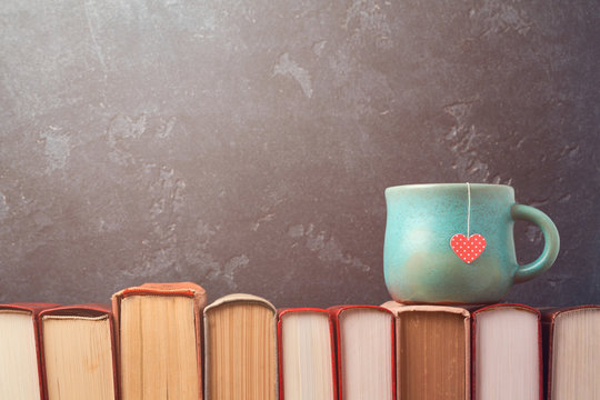 Valentines day concept with tea cup on books over blackboard background
