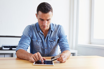 Man holding credit card and digital tablet