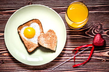 On the plate is toast with fried eggs inside a heart. Next on the plate is a little toast in the form of a heart. Next to the plate is a glass of juice and is a red decorative heart.