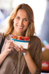 portrait d'une belle femme au marché qui achète des fraises