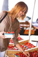 femme souriant au marché qui achète des fraises