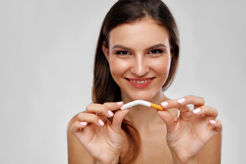 Stop Smoking. Beautiful Woman Breaking Cigarette In Half