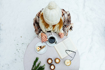 Woman holding cup of hot coffee on rustic wooden table, closeup photo  hands in warm sweater with mug, winter morning concept, top view