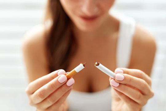Woman Hand Showing Broken Cigarette. Unhealthy Lifestyle