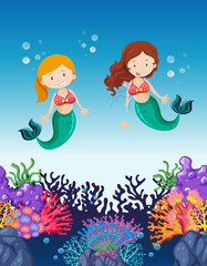 Two mermaids swimming under the ocean