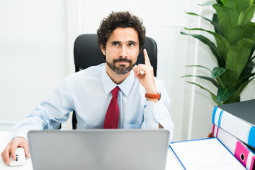 Businessman having an idea while using his computer in the office
