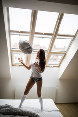 Woman play with pillow in modern bedroom near window
