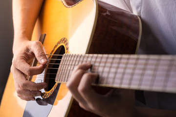 A man sitting and playing classic wooden guitar close up to chord tab fretboard.
