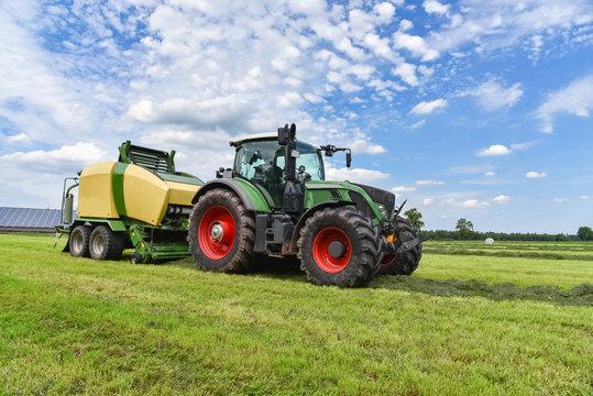 Ernte - Traktor mit Rundballenpresse im Einsatz für Grasssilage