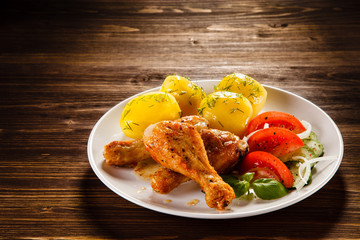 Grilled chicken legs with boiled potatoes and vegetable salad