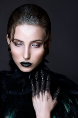 Black lips. Halloween Makeup. Luxury beautiful woman with dark lipstick and black feather collar. Beauty stylish gothic girl