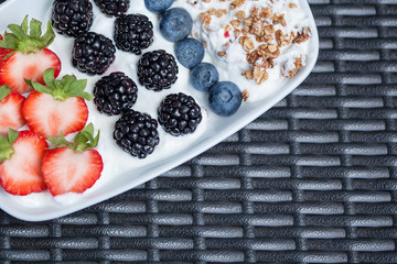 fruits granola yoghurt lying on wooden deck in plate