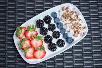 Berries granola yoghurt lying on wooden deck in plate