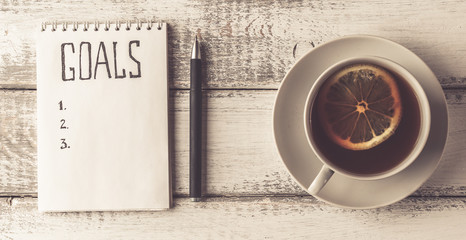 Goals concept. Notebook with goals list, cup of tea on wooden table. Motivation