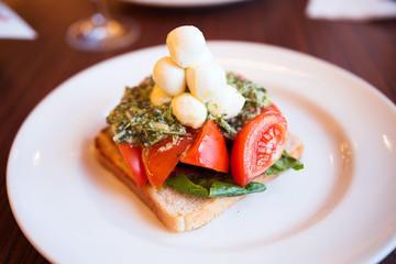 appetizer of mozzarella, toast, pesto and tomato