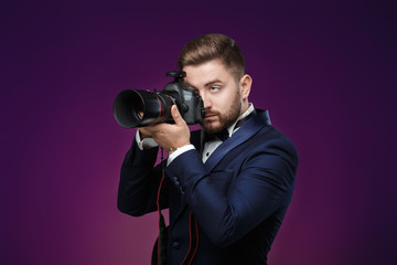 successful professional photographer in tuxedo use DSLR digital camera on dark background