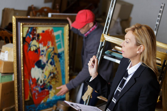 man buying painting during auction sales