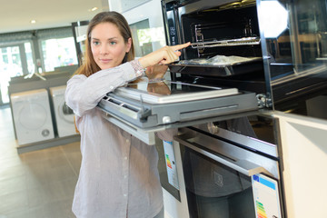 woman looking at ove in home appliance store