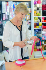Woman cutting ribbon in craft shop