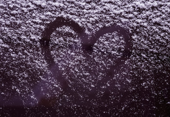 Heart on the snow-covered car windshield