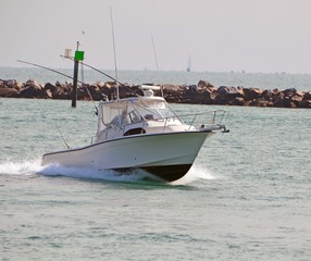 Small sport fishing boat racing through Government Cut in Miami,Florida