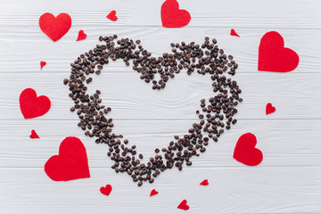Valentine's Day. Heart of coffee beans and red felt heart on a wooden background