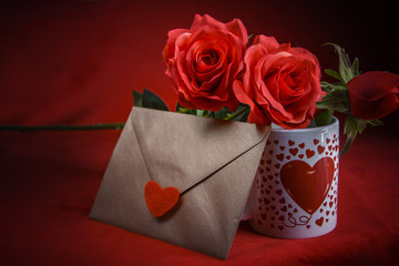 Valentine's Day: Copper gold envelope, cup of coffee and red roses on dark red background