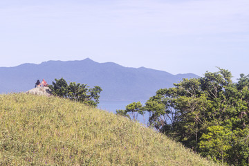 Ilhabela, Brazil, Two young people sit on top of a rock with mountains on the beackground