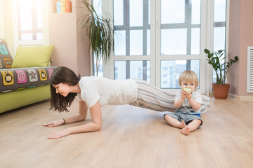 Portrait of happy mother doing exercise at home and having fun with her baby boy