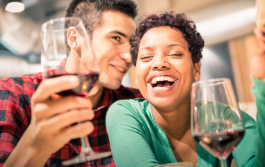 Happy multiracial lovers couple drinking red wine at fashion restaurant - Handsome man whispers soft kisses in beautiful woman ear - Relationship concept with boyfriend and girlfriend on neutral look