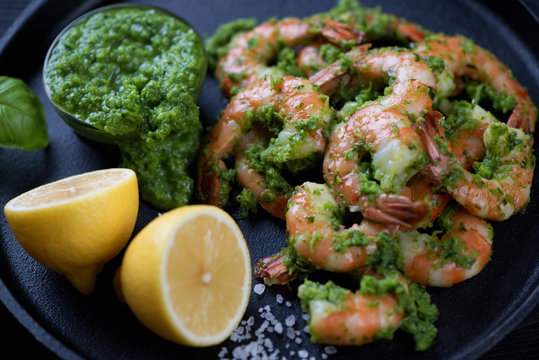 Closeup of tiger shrimps served with chimichurri sauce and lemon