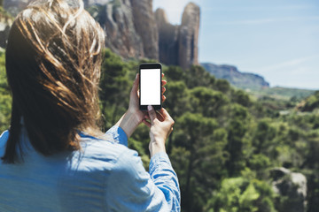 Hipster girl making photo on smartphone mobile closeup, view tourist hands using gadget phone in travel on background mountains landscape; finger touch screen cellphone mockup nature, templates
