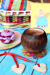 Handmade ceramic rustic pottery piala with hot chocolate (cocoa), two decorative hearts on a red ribbon and handmade fabric cake on plate on blue wooden boards