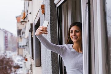 Beautiful girl taking selfie at home