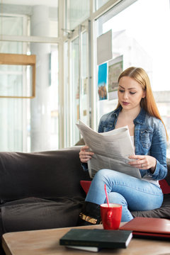 Young woman reading newspaper and having coffee break.