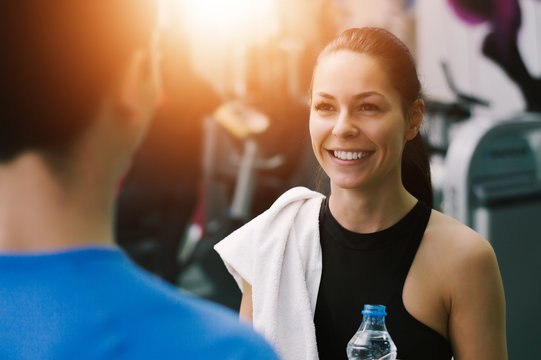 Young woman talking to her fitness trainer in the gym smiling