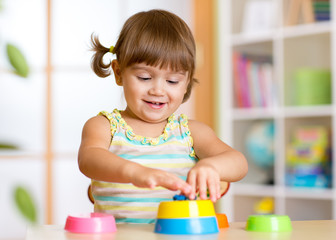 kid little girl playing with toys at home