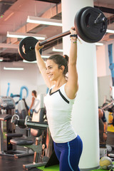 Young athletic woman lifting weights in a gym.