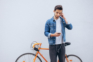 Young student standing near the bicycle looking at phone and listening to music