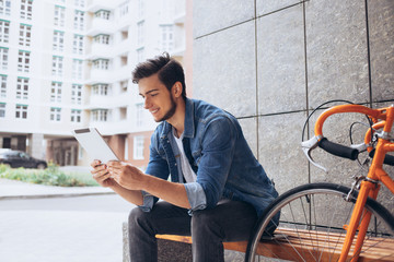 Young man using the tablet sitting on the bench