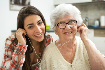 Granddaughter listening music with her grandmother at home.