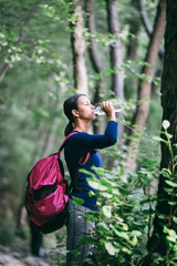 Beautiful sporty woman enjoying in untouched nature hiking and outdoors adventure. She standing on forest footpath and holding bottle of water.