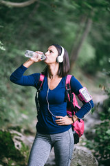 Beautiful sporty woman enjoying in untouched nature hiking and outdoors adventure. She listening to music with headphones and holding bottle of water.
