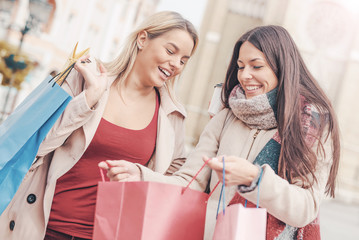 Young women shopping together. Consumerism, shopping, lifestyle