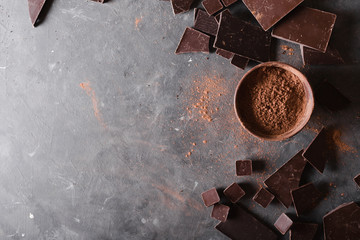 Chocolate  chunks and cocoa powder. Chocolate bar pieces.  A large bar of chocolate on gray abstract background. Background with chocolate. Slices of chocolate, Sweet food photo concept. Copyspace