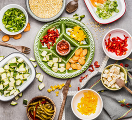 Healthy food preparation: gut colorful vegetables on green plate and bowls with barley seeds and feta. Salad or stew ingredients.