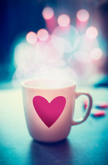 Romantic lifestyle with mug and heart at bokeh background, front view. Love symbol or Valentines day concept
